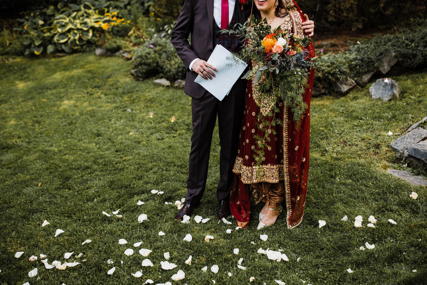 groom holds paperwork as bride and groom stand among rose petals