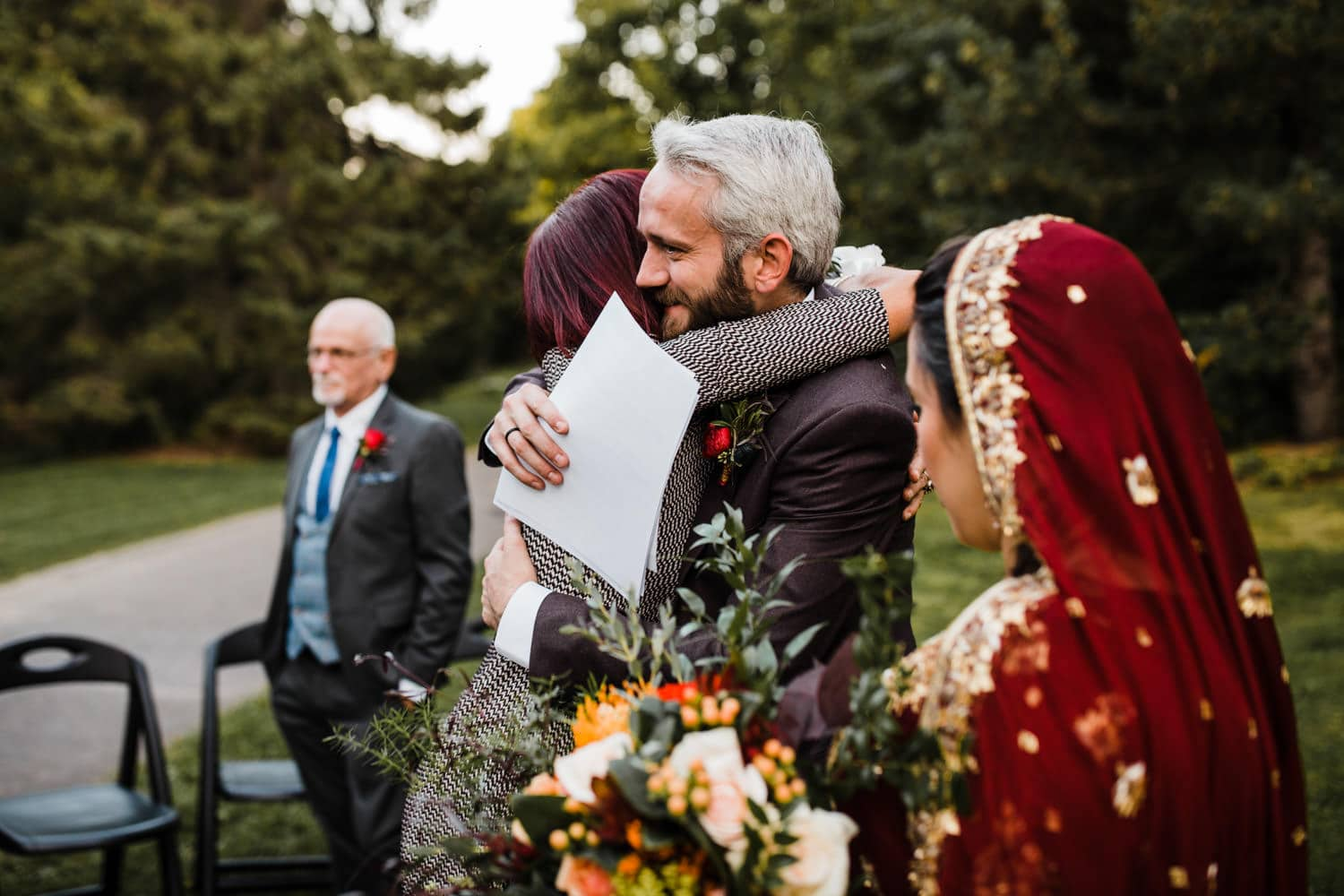 groom hugs family after intimate outdoor ceremony