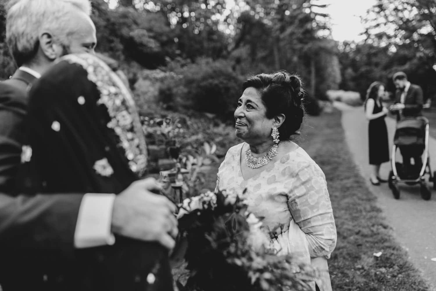 mother of the bride looks lovingly at bride and groom after intimate outdoor ceremony
