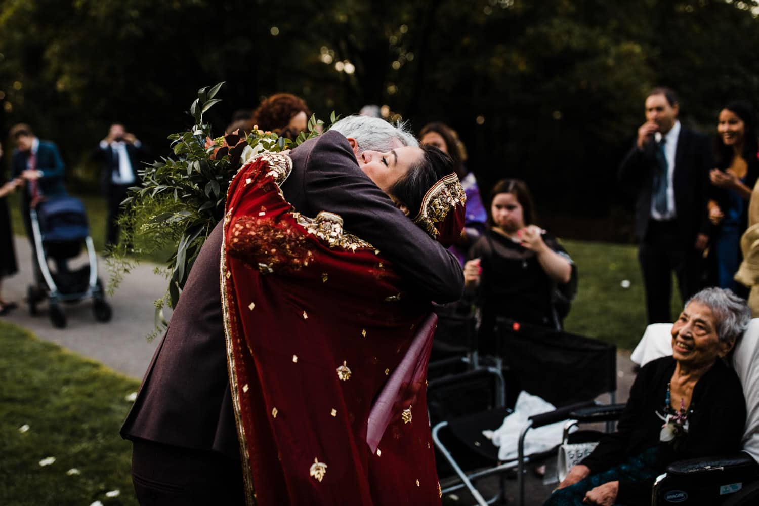 bride and groom hug one another after intimate outdoor ceremony