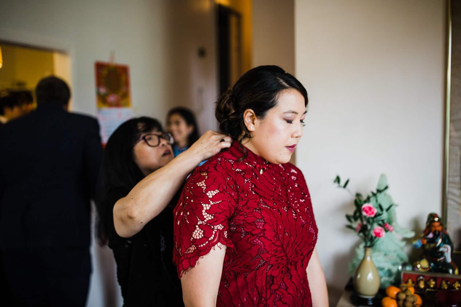 bride puts on her red dress for tea ceremony