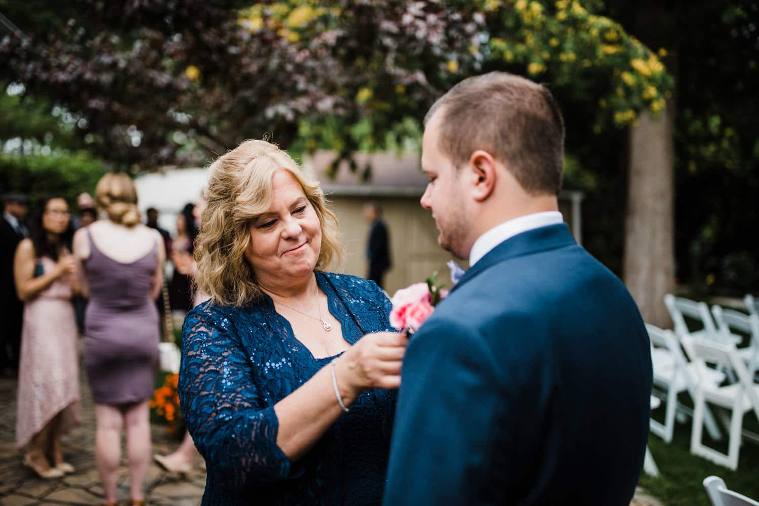 groom's mother adjusts boutonniere