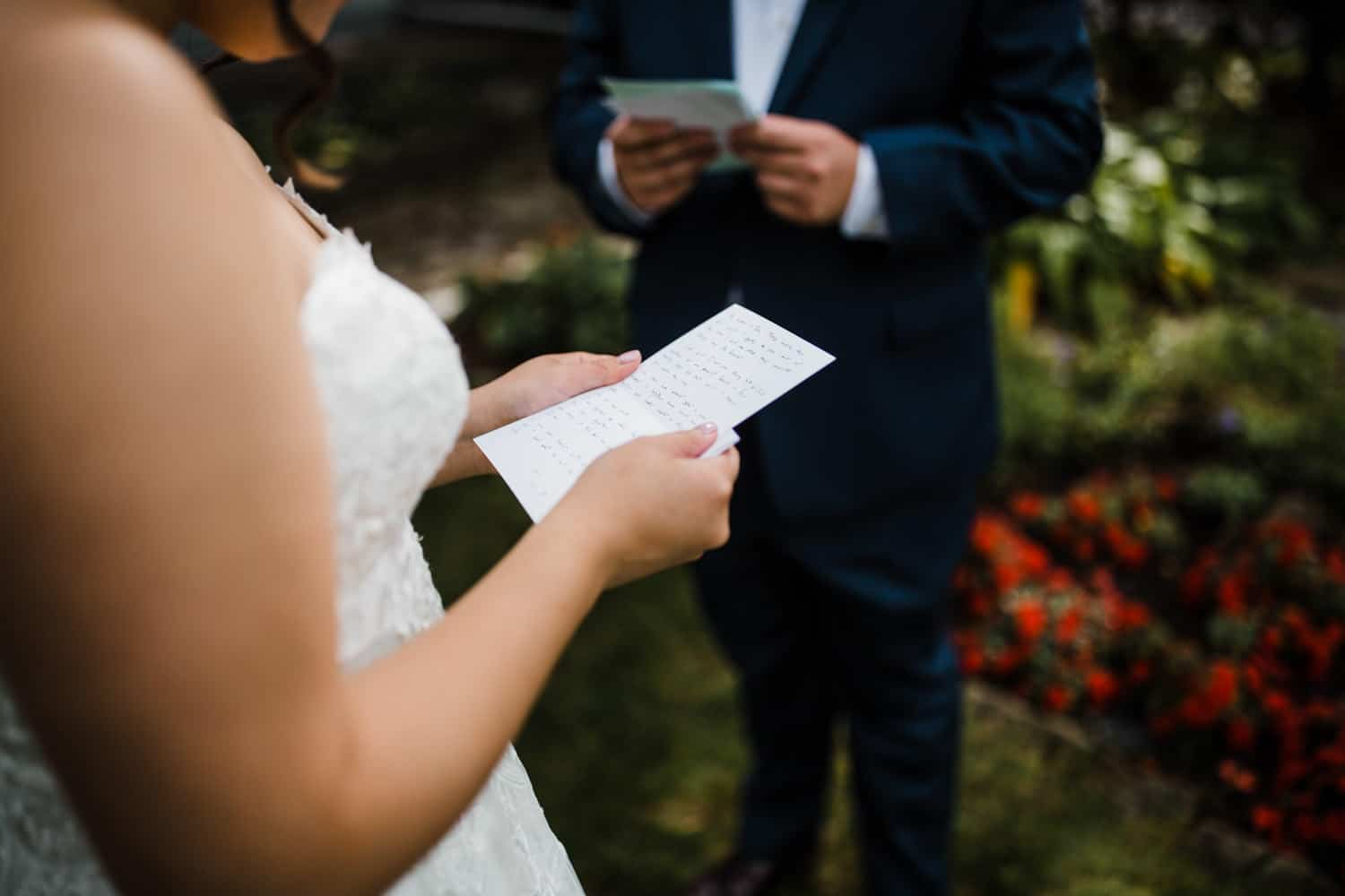 bride and groom read letters to each other - small ottawa backyard wedding