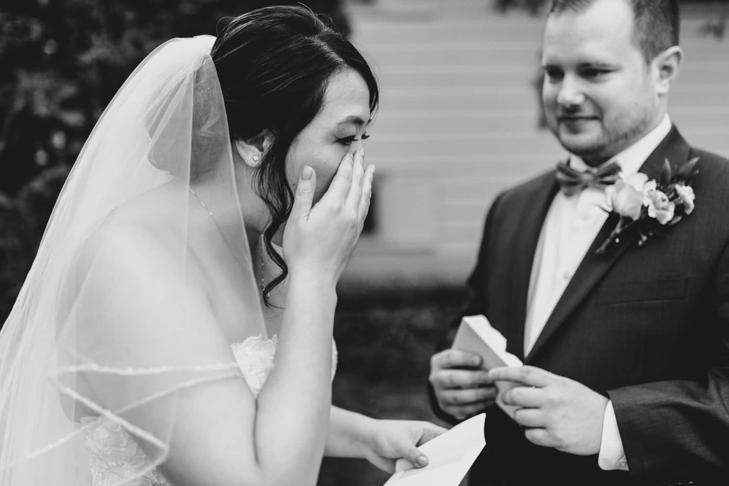 bride wipes tears from her eye after reading letter from groom - small ottawa backyard wedding