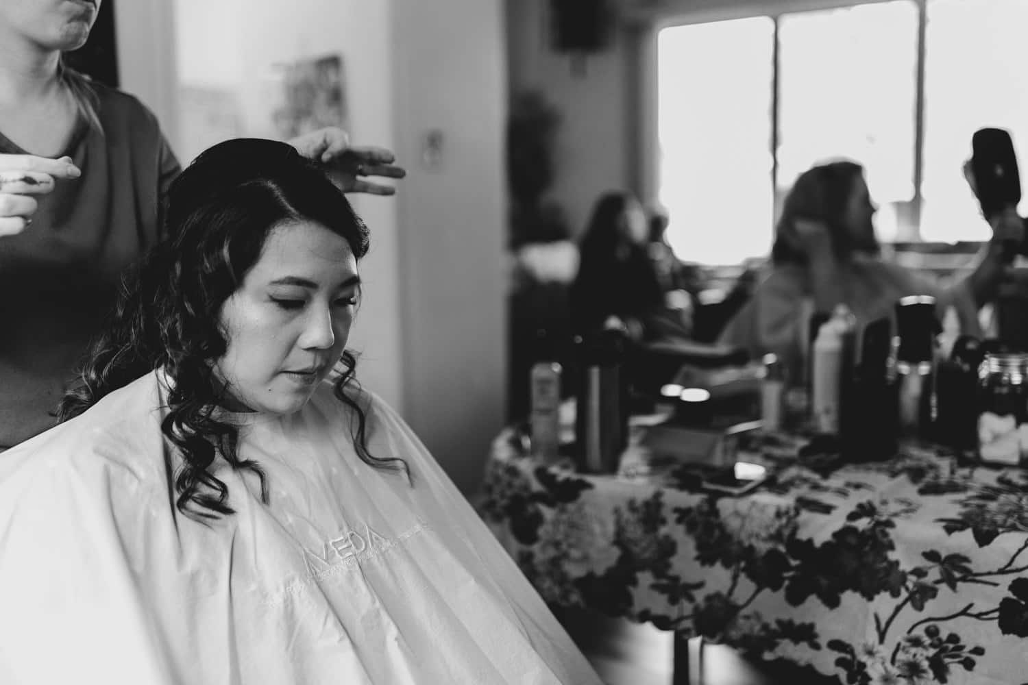 bride gets her hair done the morning of her wedding