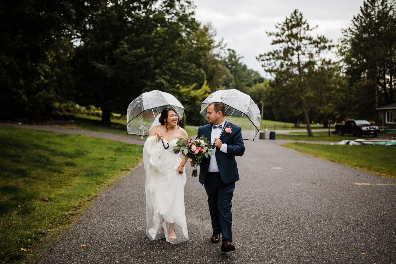 bride and groom walk down the street with umbrellas - small backyard wedding ottawa