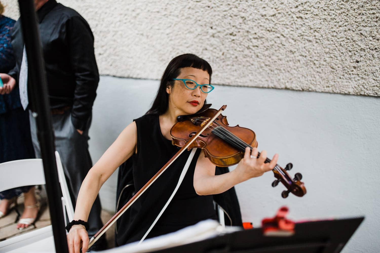 violinist plays during backyard wedding