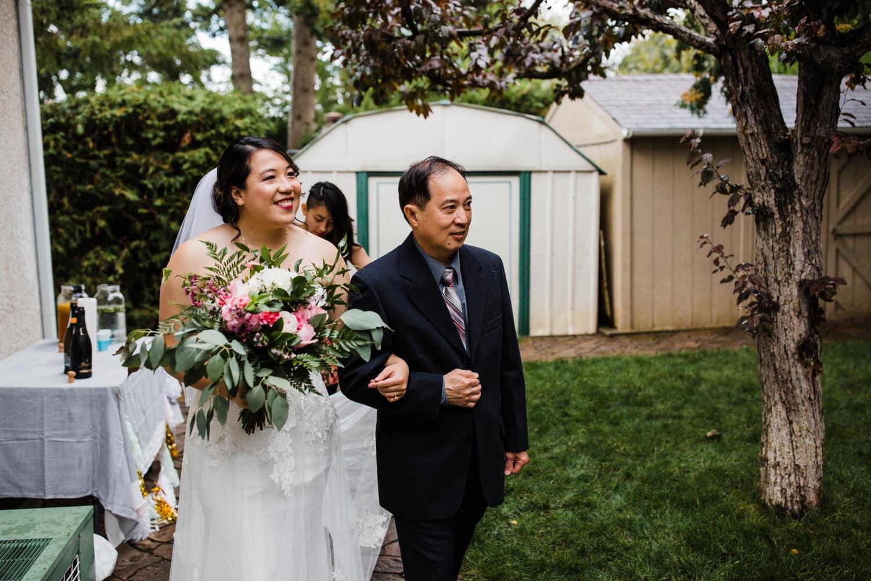 bride walks into backyard ceremony