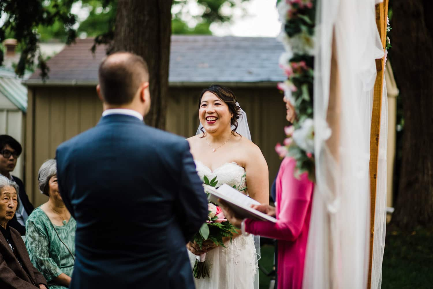 bride laughs during ceremony - small ottawa backyard wedding