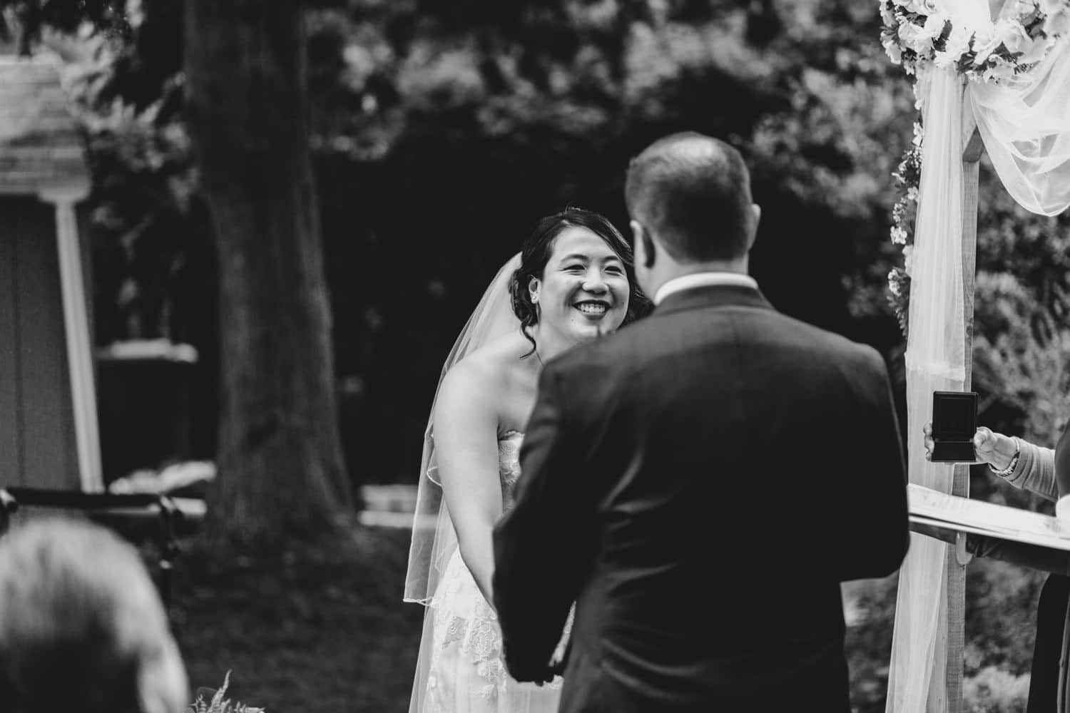 bride laughs during backyard wedding ceremony