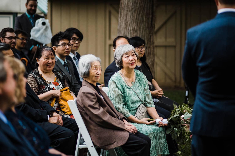 family watches backyard wedding ceremony