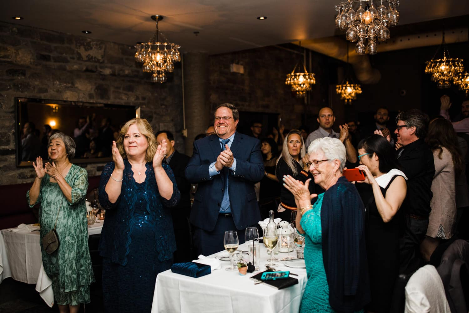 guests give bride and groom standing ovation - sidedoor wedding reception