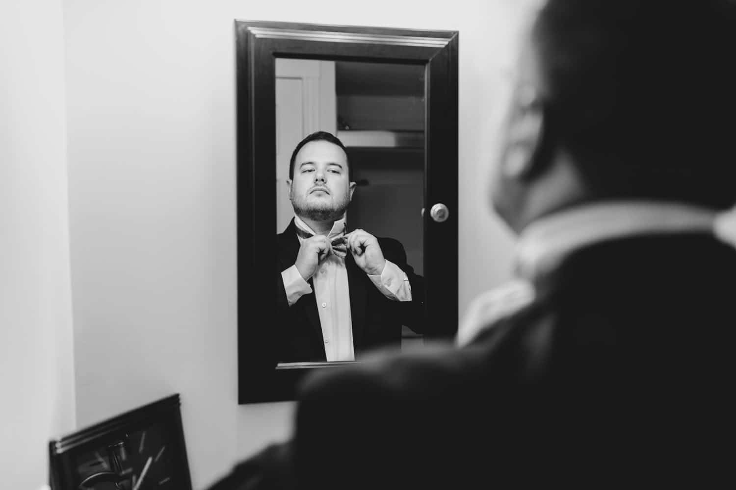 groom adjusts his bow tie in a mirror