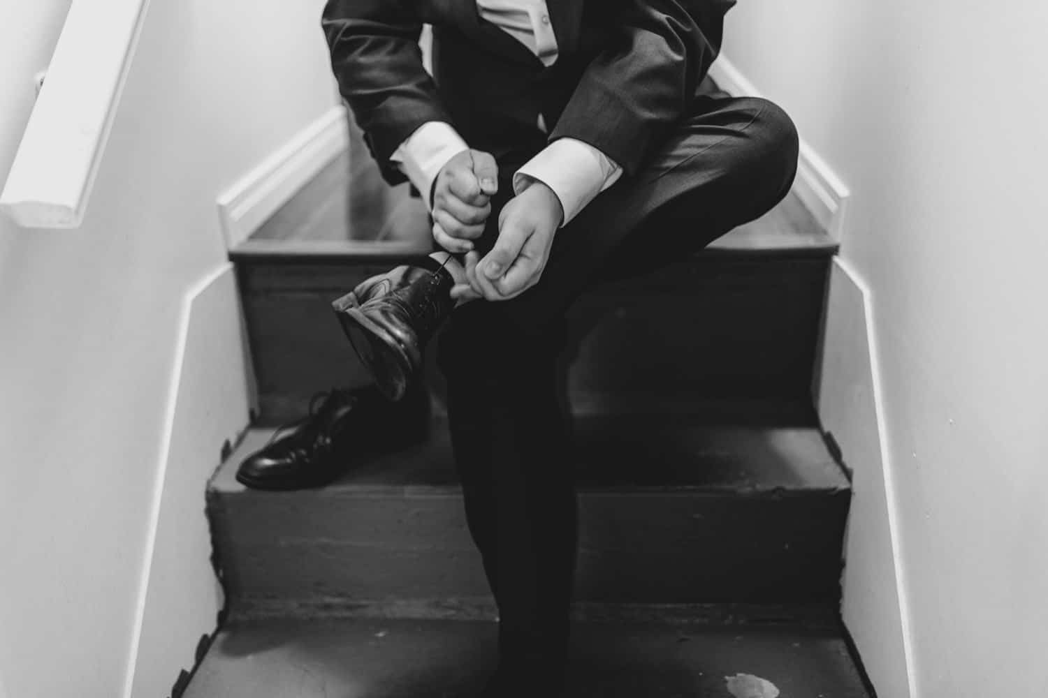 groom sits on stairs and ties his shoes