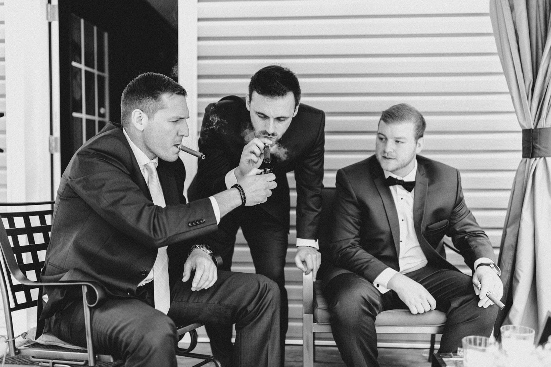 groom lights his cigar with groomsmen