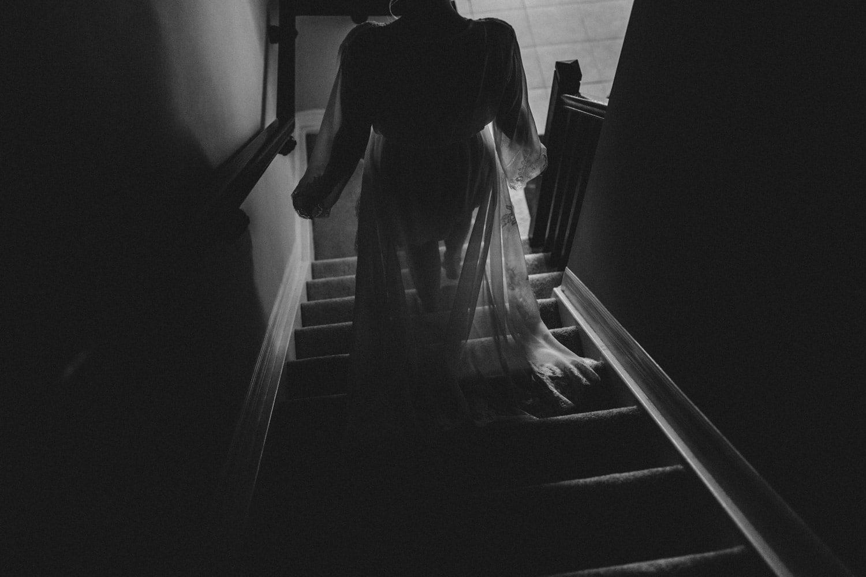 bride walks down stairs in robe