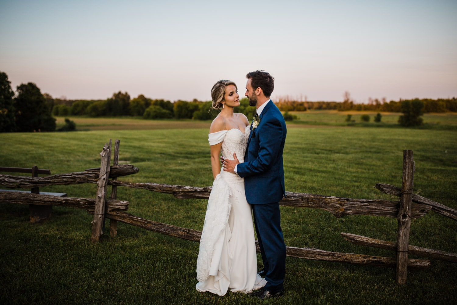 bride and groom stand by wooden fence - strathmere wedding