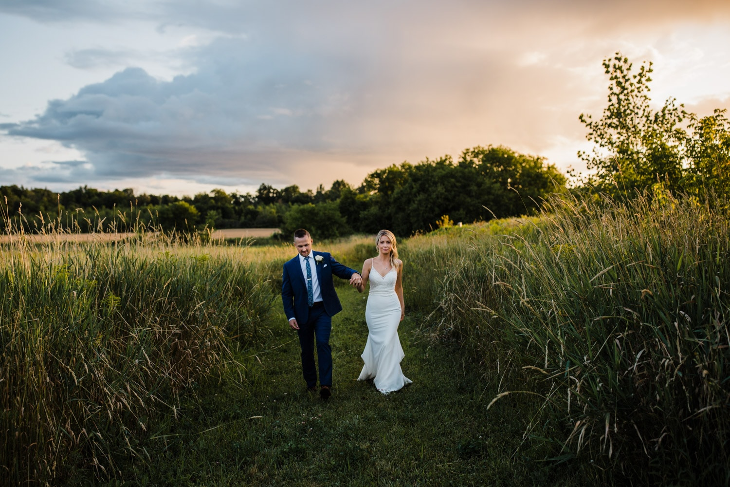bride and groom walk through field together at sunset - ottawa wedding photographer