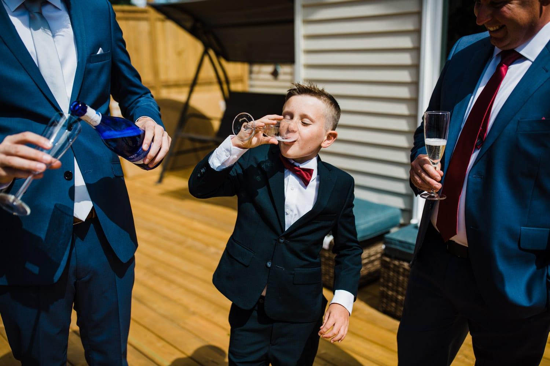 ring bearer drinks champagne