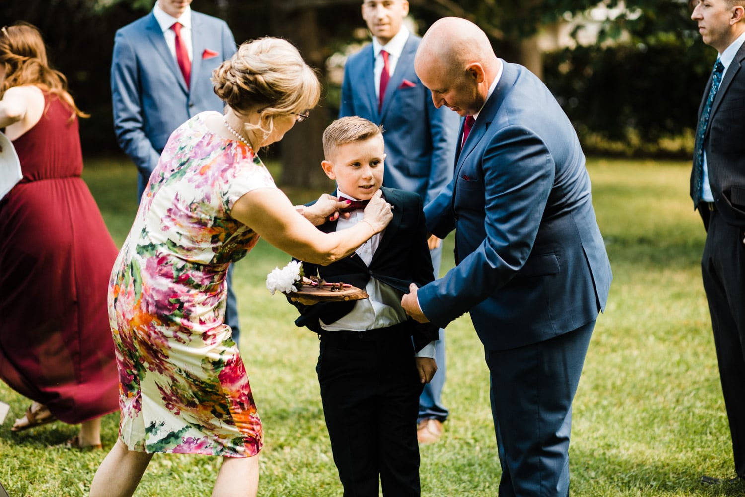 family adjusts ring bearers suit before ceremony