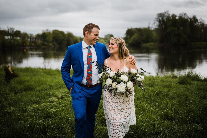 bride and groom walk through grass together
