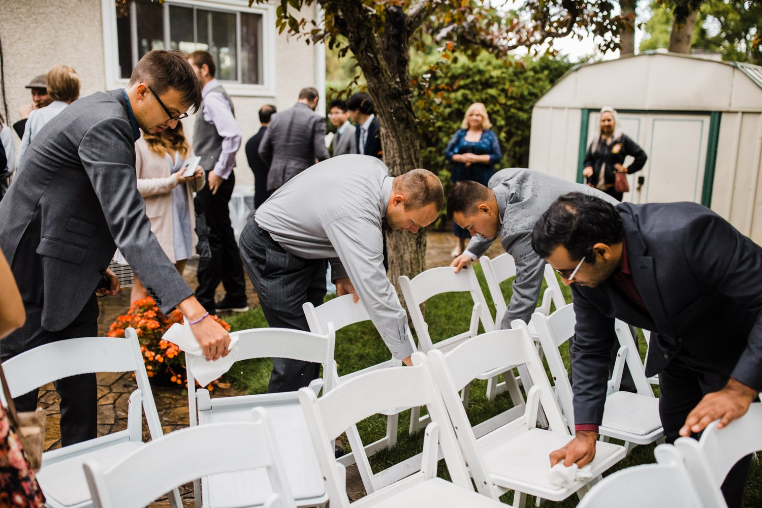 guests clean off chairs after rain - ottawa backyard wedding