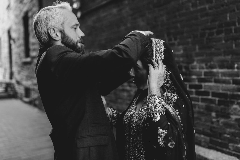 groom helps bride with her veil