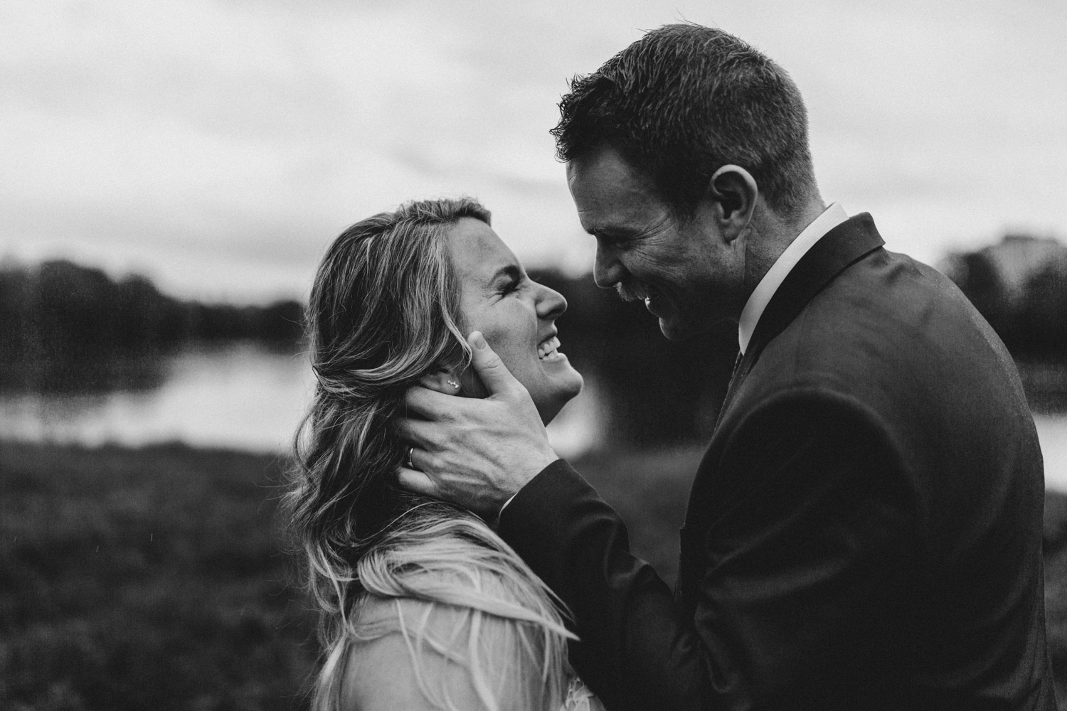 bride and groom laugh together outside