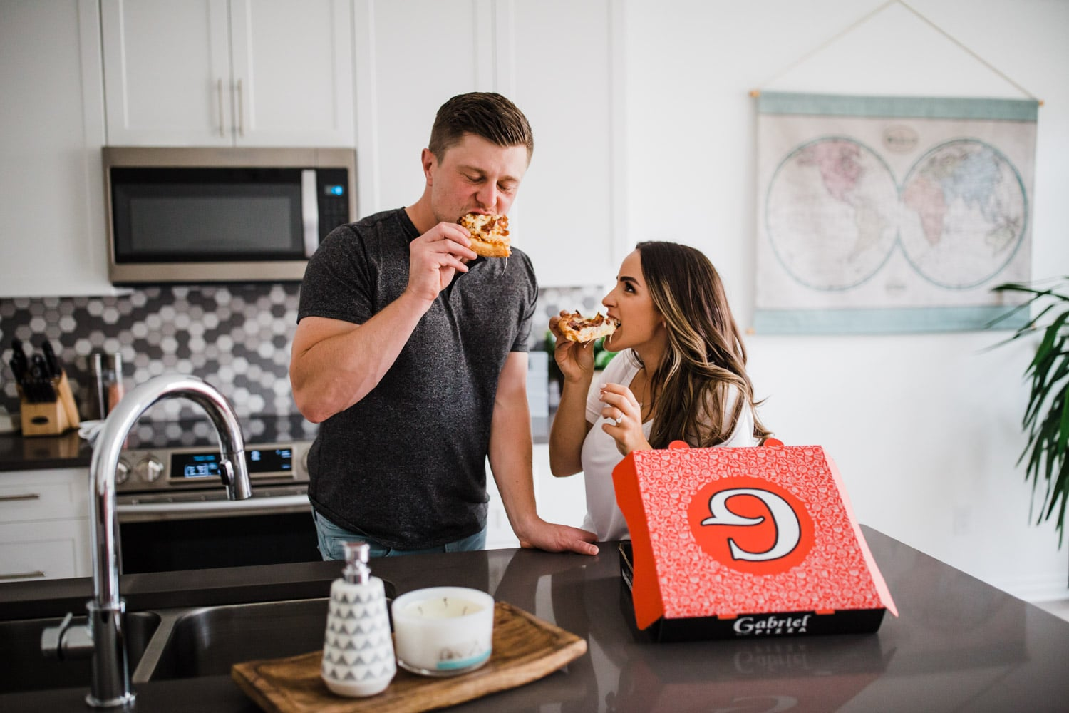 couple eat pizza together in kitchen - ottawa engagement photographer