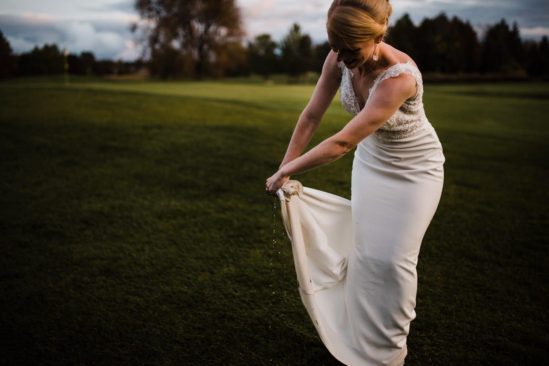 bride wrings out dress - ottawa wedding photographer
