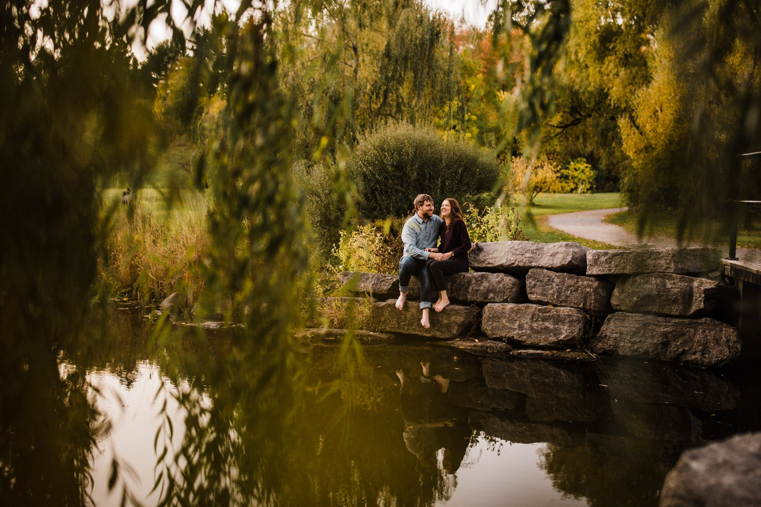 couple sit by pond and laugh together