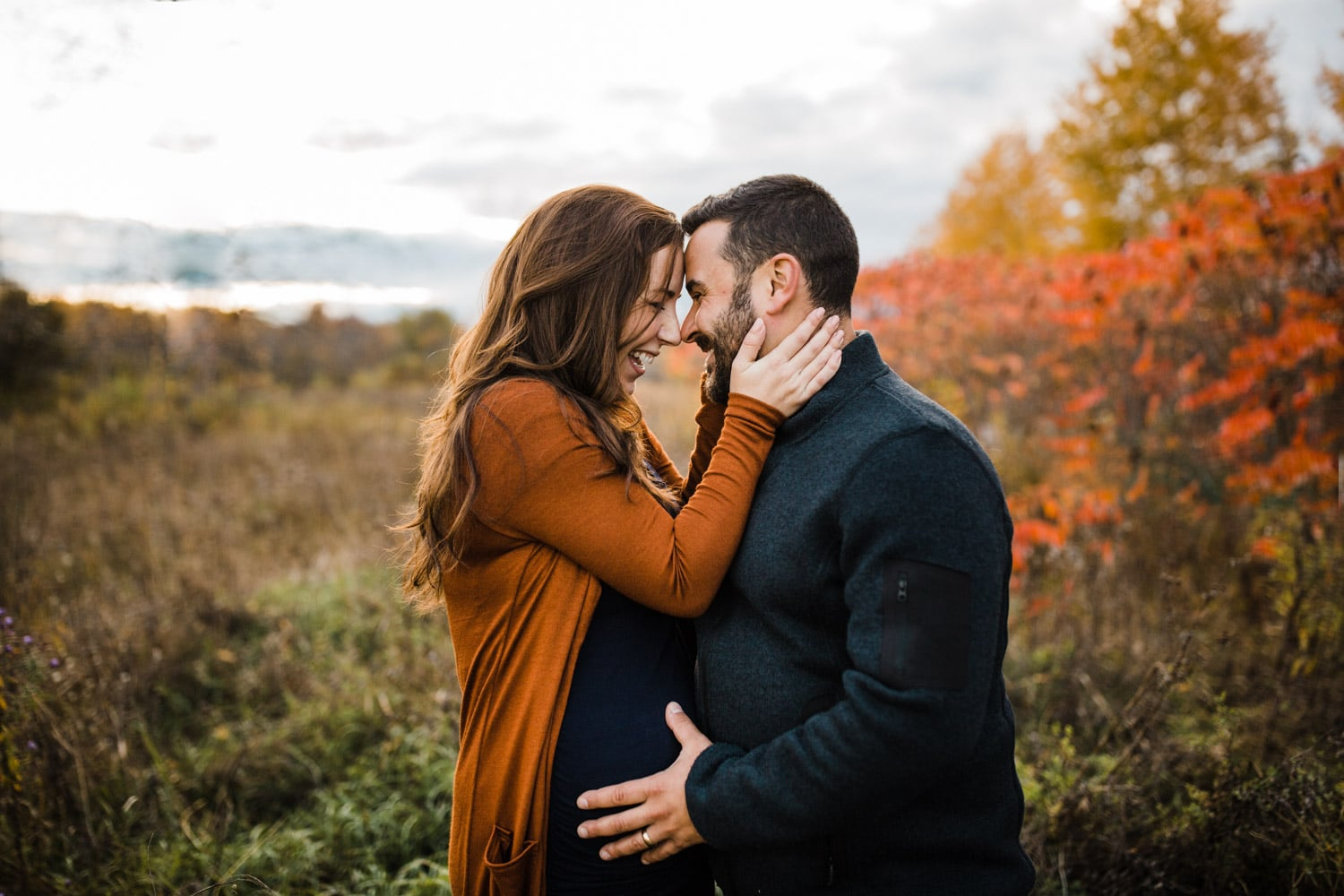 expectant couple laugh together outside