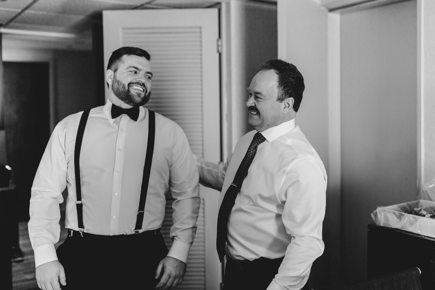 groom laughs with his dad while getting ready