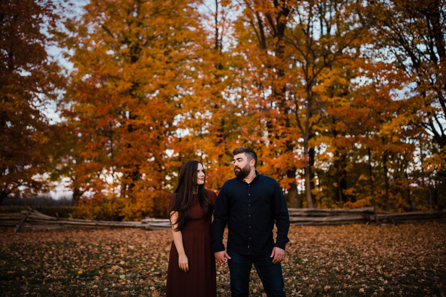 couple stand together infront of gorgeous fall trees