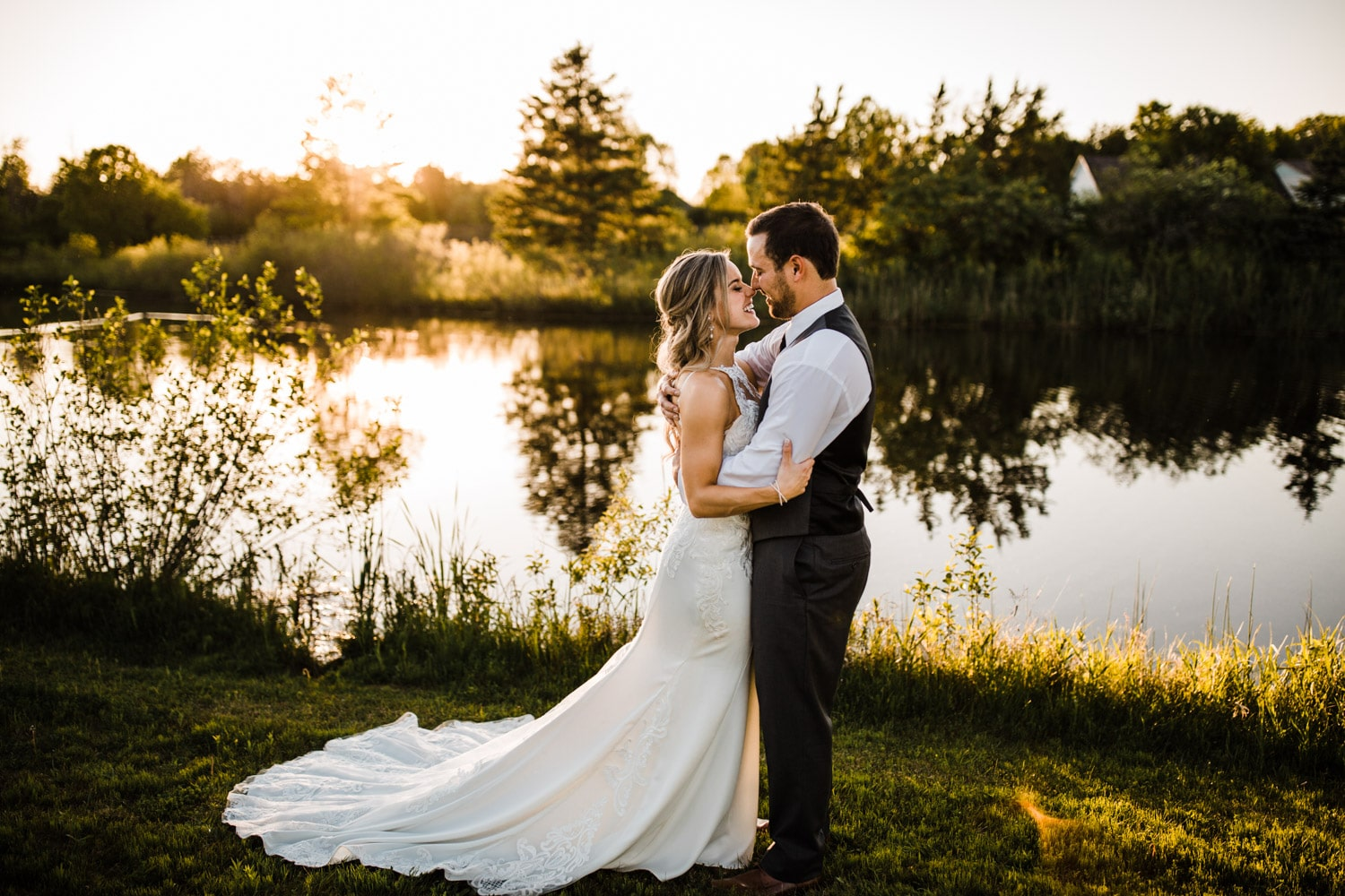 bride and groom stand together by pond - ottawa wedding photographer