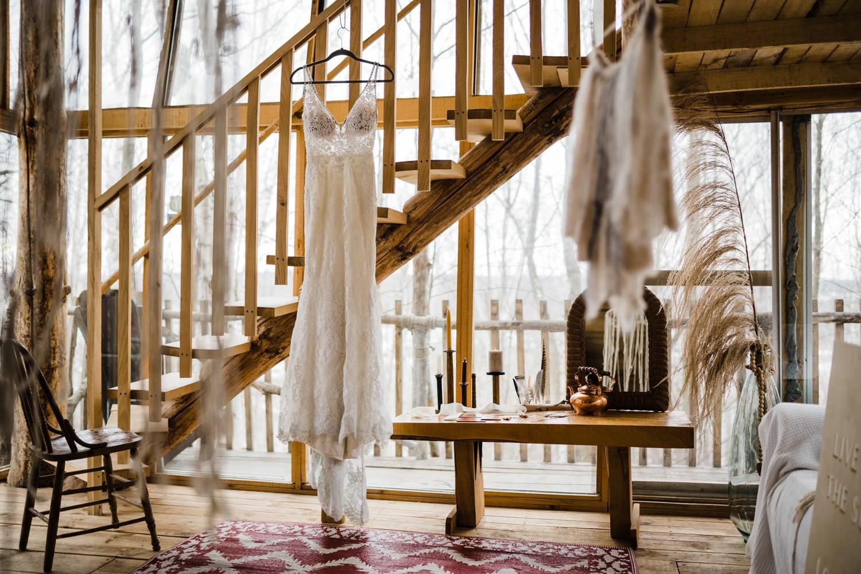 wedding dress hangs on cabin stairs - boho elopement