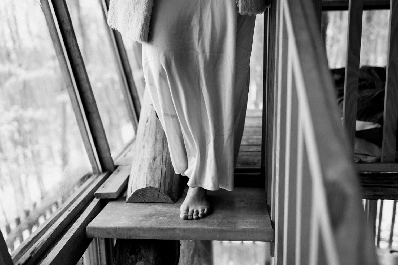 bride walks down wooden stairs in cabin - boho elopement