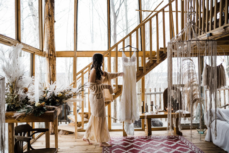 bride reaches towards wedding dress - boho elopement
