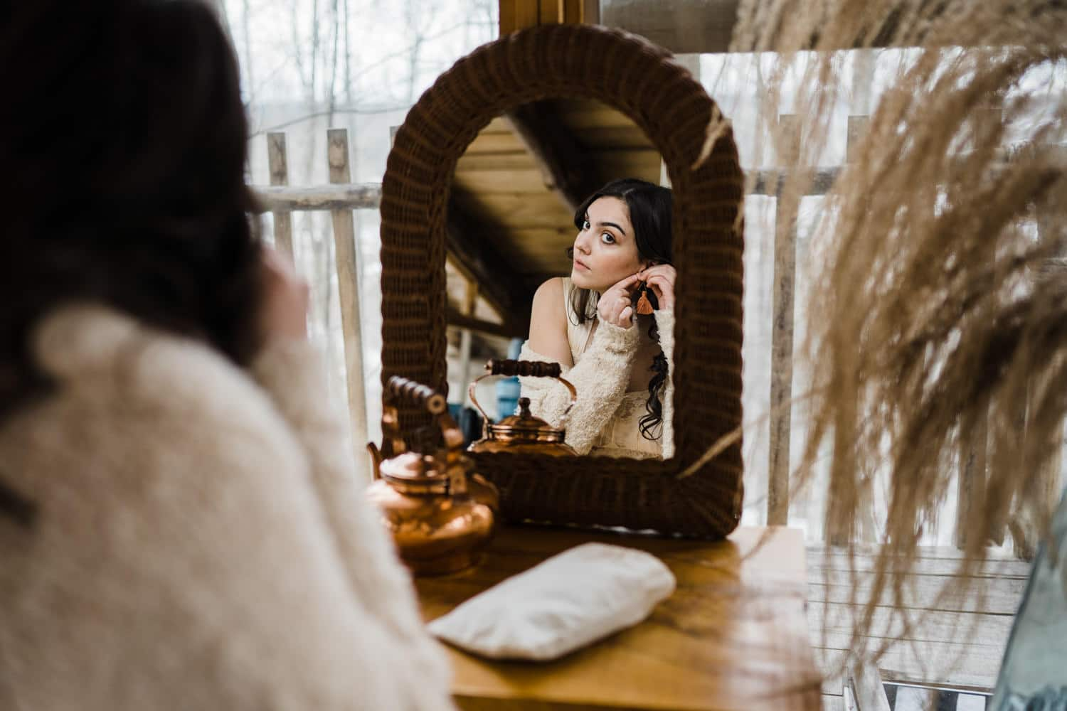 bride looks in mirror and puts earrings on