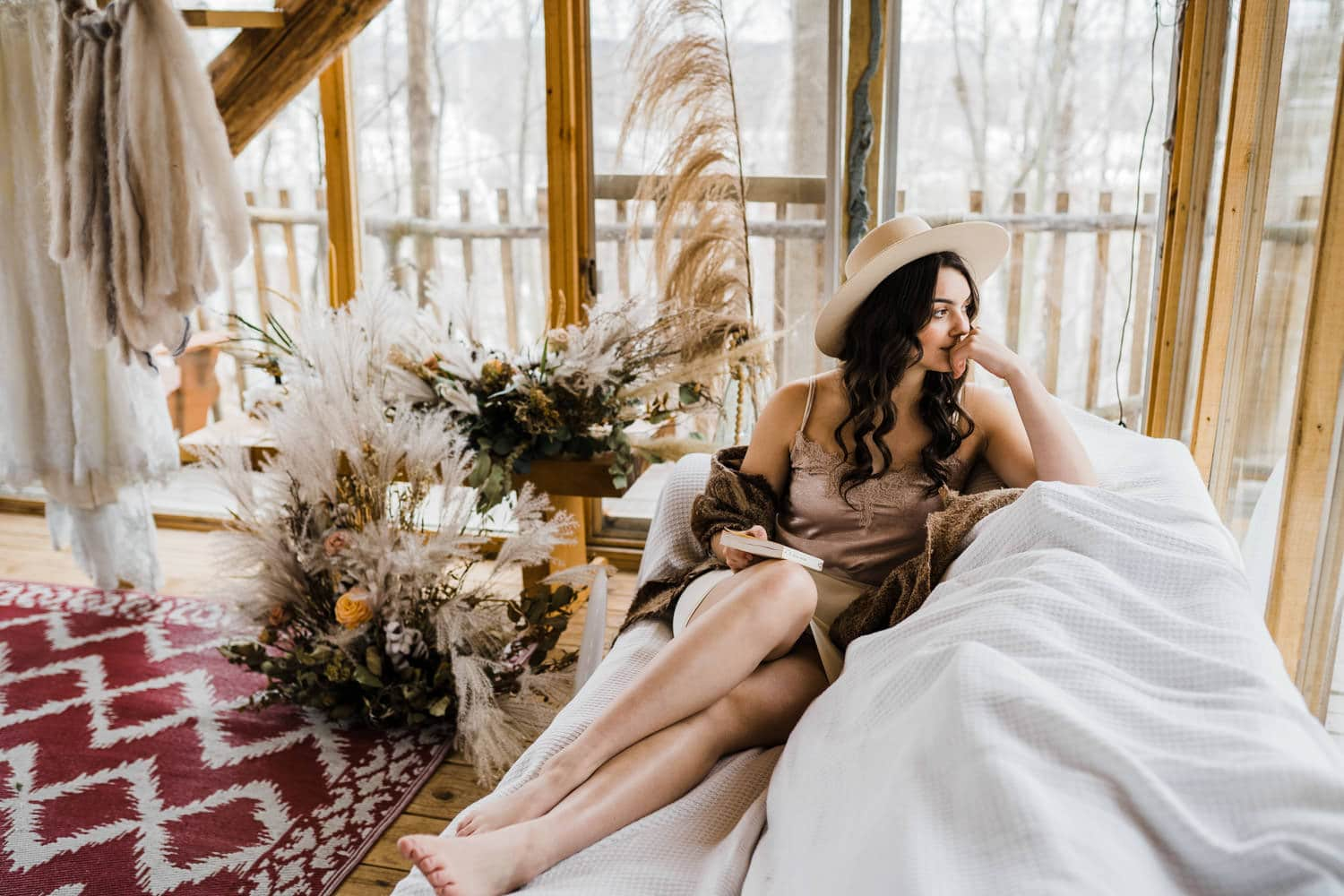 bride sits on couch and looks out window - cabin in the woods - boho elopement