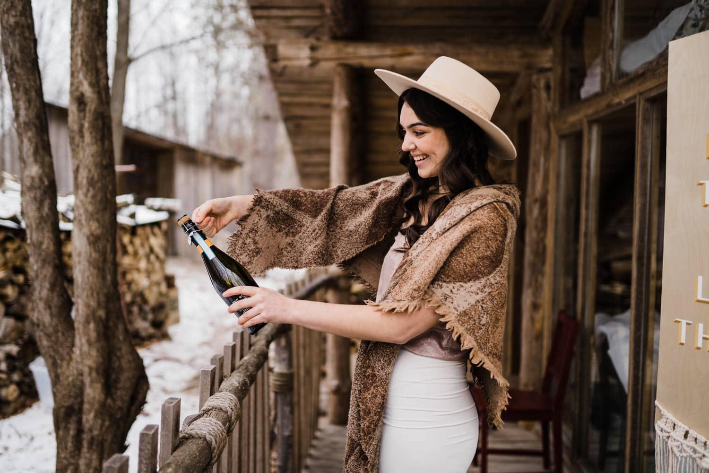 bride pops champagne bottle - cozy cabin elopement