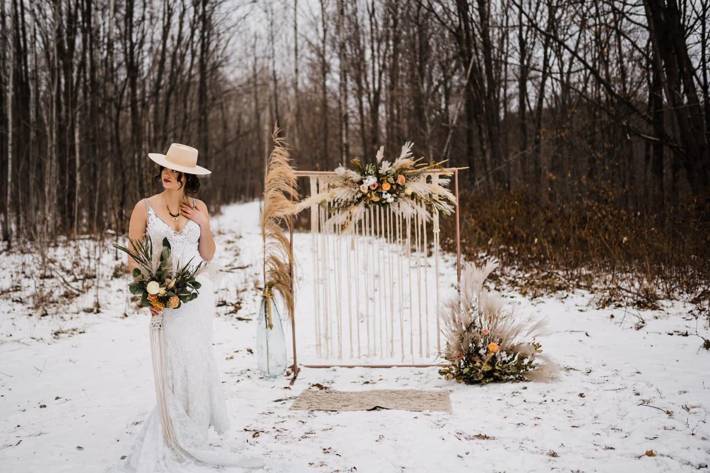 bride stands next to winter elopement arbour