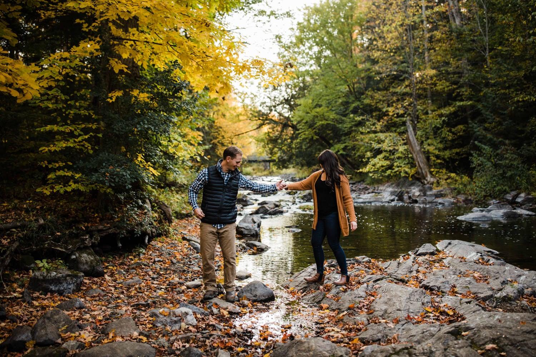 couple walk over rocks together outside