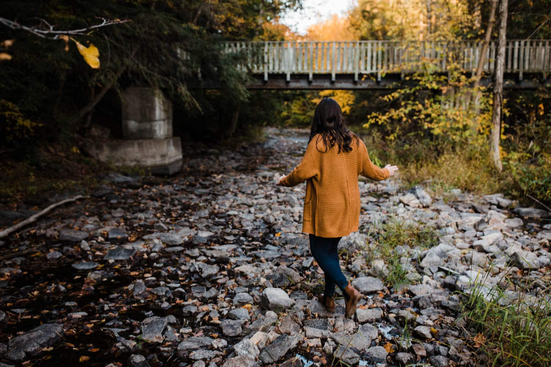 woman walks over rocks towards bridge