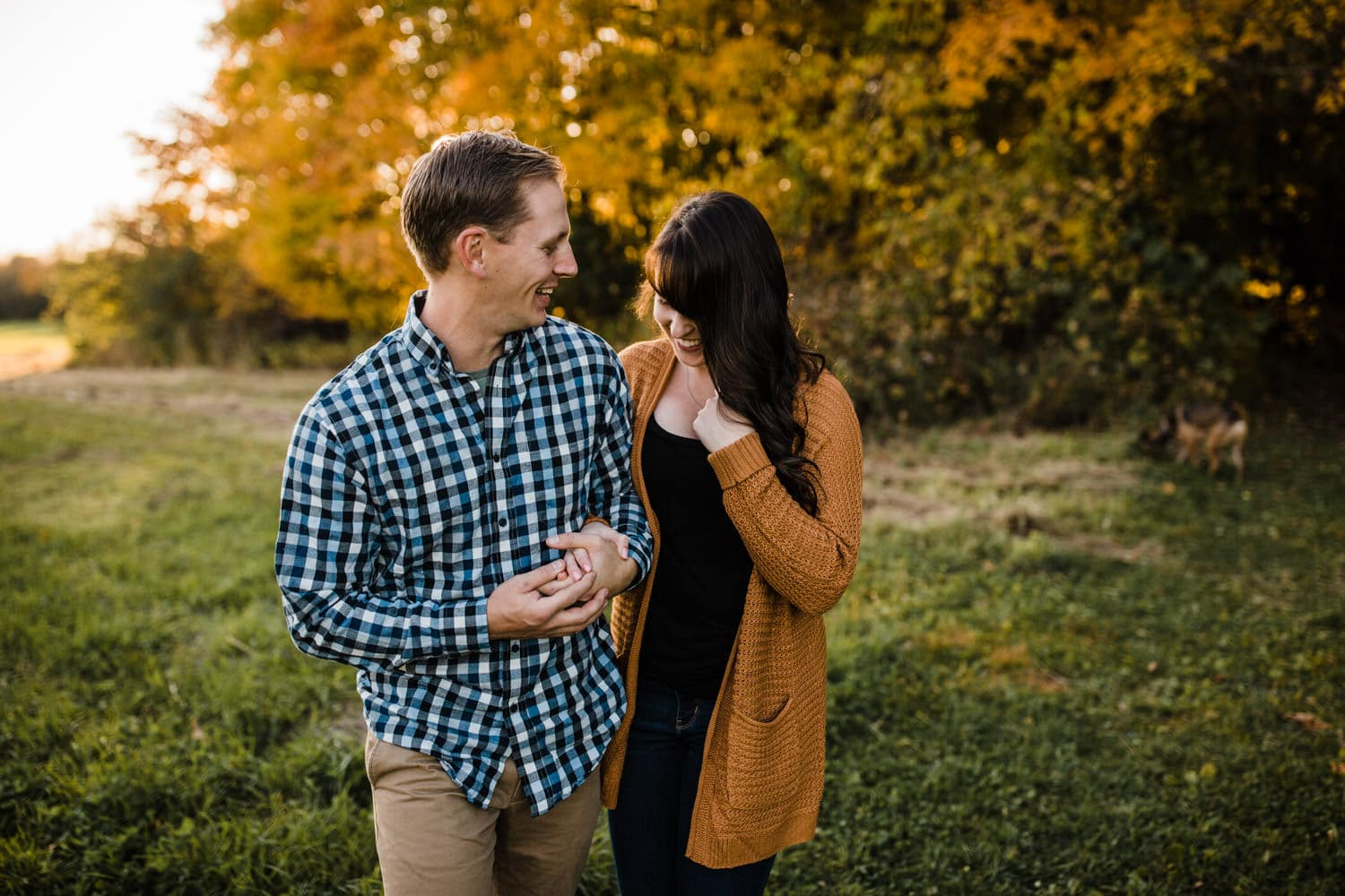 couple laugh together walking through field - mill of kintail engagement - fall engagement