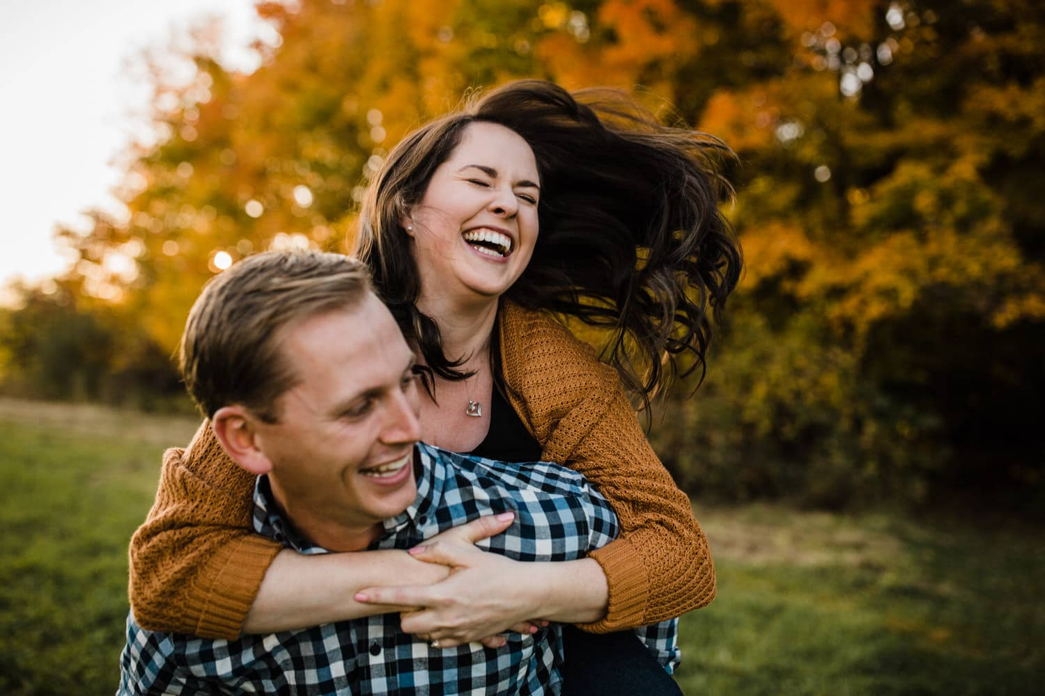 woman laughs while man gives her a piggy back ride - mill of kintail engagement