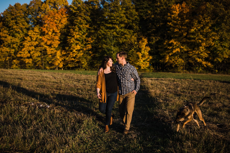 couple walk through open field during sunset