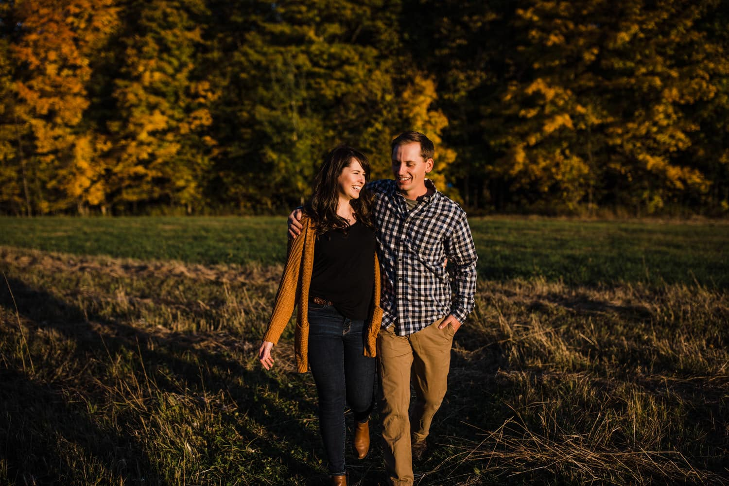 couple laugh and walk together through a field at sunset - mill of kintail engagement
