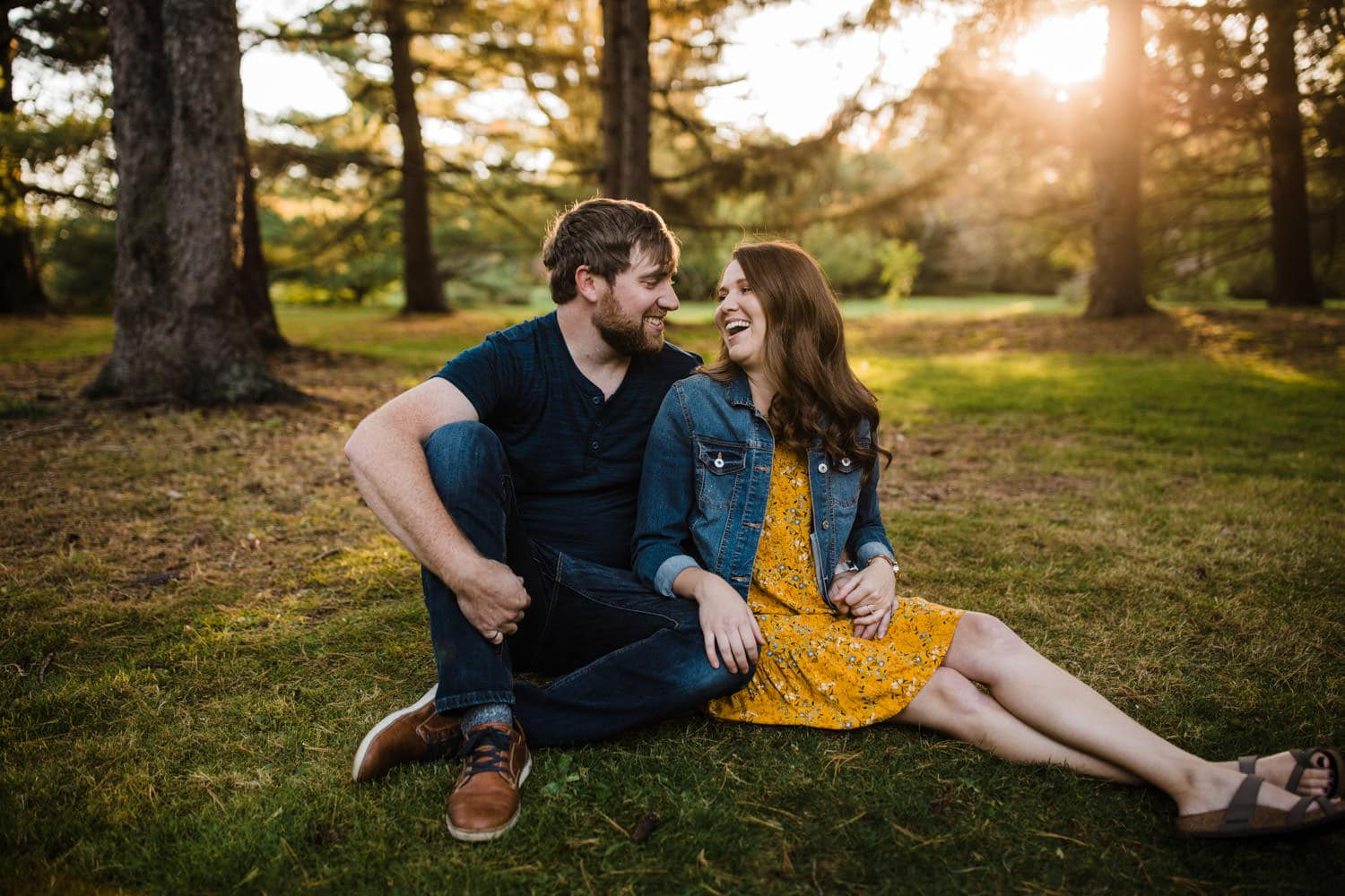 couple sit and laugh together in park at sunset - ottawa arboretum engagement