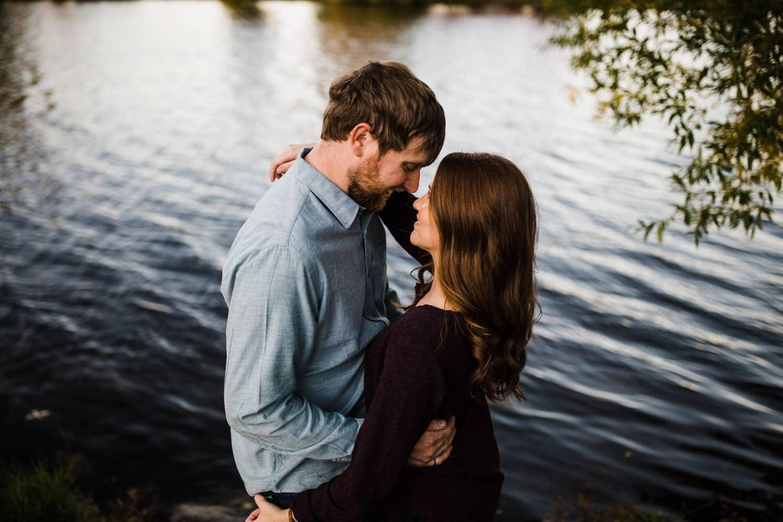 couple stand at water's edge - ottawa arboretum engagement